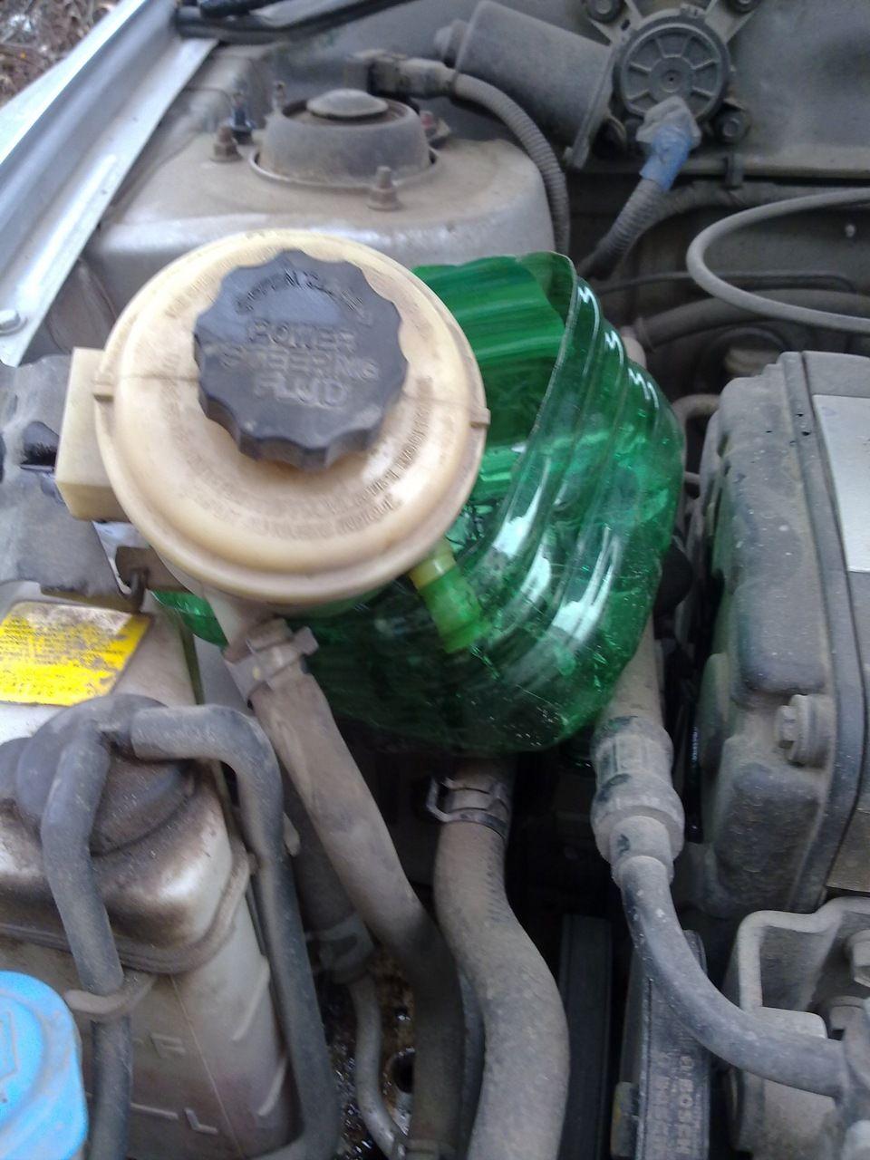 Если высосали не всю жидкостьс бачка гур, снимаем его и сливаем в емкость.