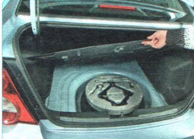 Инструменты для замены колеса находятся в багажнике Шевроле Авео